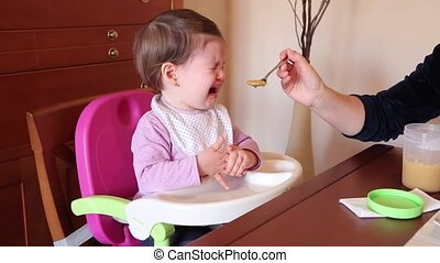 Baby girl crying with spoon food - Baby girl sitting on...