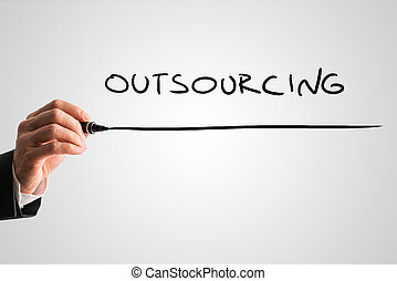 Man writing the word Outsourcing with a black marker pen...
