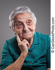 Old woman thinking. Elderly woman is isolated on dark...