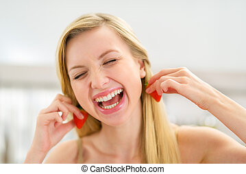 Portrait of happy young woman using strawberry as earring