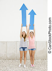 Teenagers pointing blue arrows - Beautiful and happy...