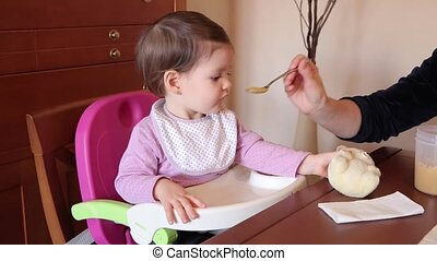Happy baby girl eating with a spoon food - Happy baby girl...