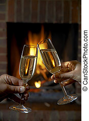 Couple With Glass Of Champagne Relaxing By Fire
