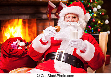 My favorite meal! Cheerful Santa Claus holding glass with...