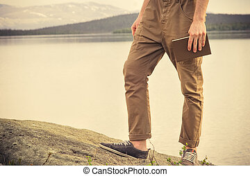 Young Man with book outdoor Education and Lifestyle Travel concept nature on background