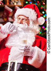 I love milk! Cheerful Santa Claus holding glass with milk...