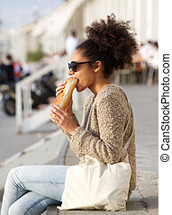 Young woman relaxing outdoors and eating food - Portrait of...