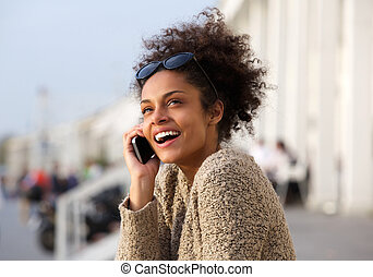 Close up portrait of a young woman smiling with mobile phone...