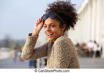 Attractive black woman smiling outdoors - Close up portrait...