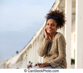 Young woman smiling outdoors and listening to music - Close...