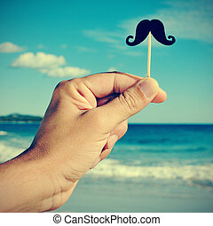 man hand with a fake moustache on the beach, with a filter...