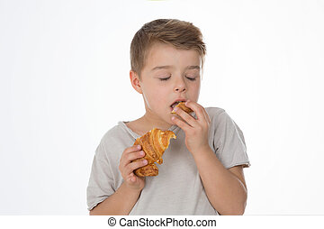 dreaming child  - kid tastes a piece of croissant