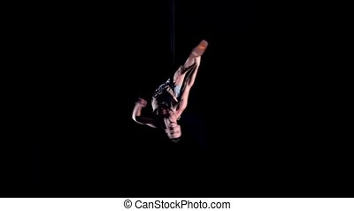 Young man air gymnast on black background