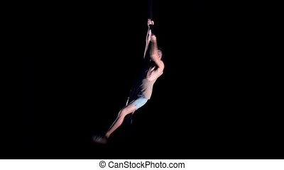 Young man air gymnast on black background.