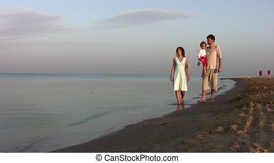 walking family with girl on beach