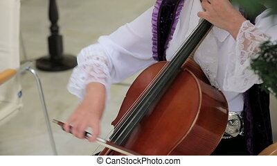 Woman Playing the Violoncello - Two frames. Close-up shot of...