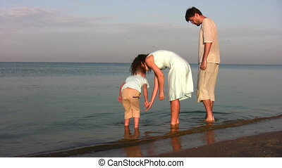 family with boy searching shells