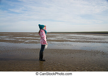 lonely child during mudflat hiking tour in northern sea