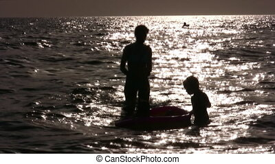 silhouette mother with children in water