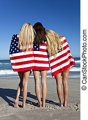 Three Young Women Wrapped in American Flags on a Beach -...