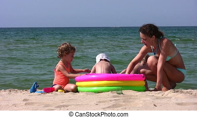 mother with children play on beach
