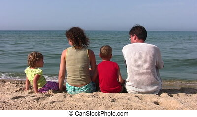 behind family of four sitting on beach