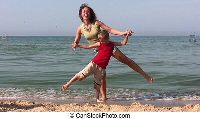 mother and son stand on one leg on beach - Mother and son...