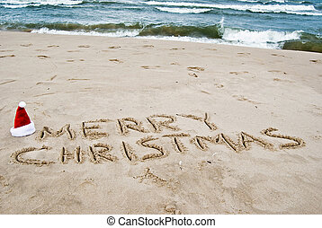 Merry Christmas - Santa hat and holiday greeting in sand.