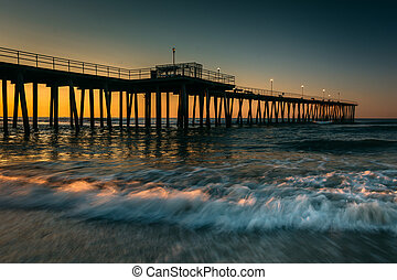 Fishing pier and waves on the Atlantic Ocean at sunrise in...