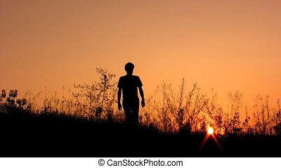 walking man silhouette on sunset sky alone - Silhouette of...