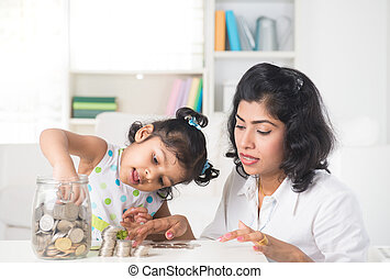 indian Mother and daughter putting coins into bottle, saving...