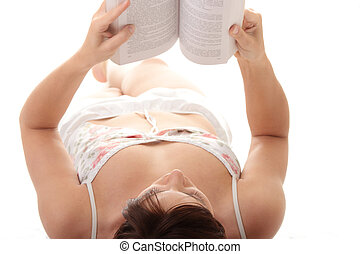 Pretty young girl in pyjamas with book in hands