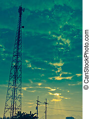 Communication Antenna Tower and Cloudy Sky with Sunbeam -...