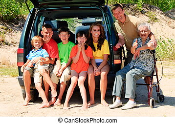 Happy family by car - Whole family by their car looking at...