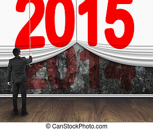 businessman pulling down 2015 curtain to cover old dark 2014...