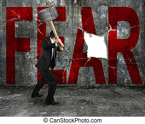 businessman holding sledgehammer hitting red FEAR word on...