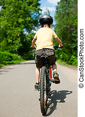 Kid riding bicycle - Young boy riding bicycle, shallow dof