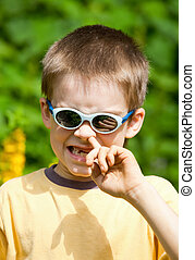 Kid picking his nose - Portrait of a young boy wearing...