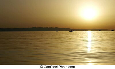 Small boats at sea in sunset - Scenic view at small boats on...