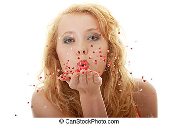 Pretty young woman blowing a kiss with a swirl of hearts on...