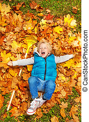 Boy laughing and laying on autumn leaves with rake - Boy...