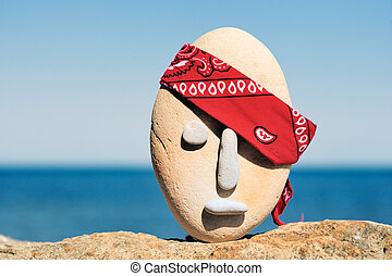 Bandana - Symbol of stone head with a patterned red bandana...