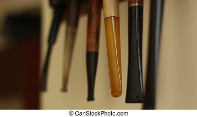 Tobacco Pipe - Tilt shot of vintage tobacco pipes, hung on...