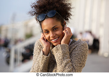 Happy young woman listening to music on headphones outdoors...