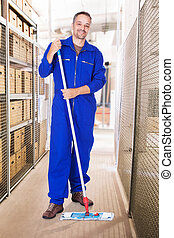 Smiling Worker Cleaning Warehouse With Mop - Full length...