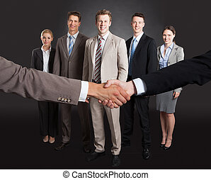 Businessmen Shaking Hands With Confident Team Standing...