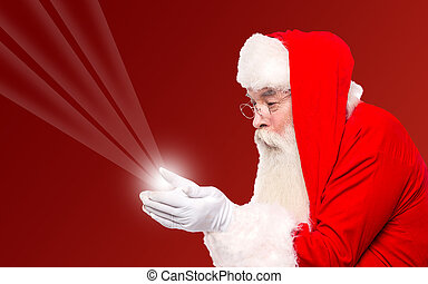 Santa holding magical lights in hands - Santa claus showing...