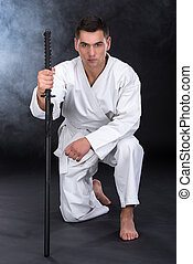 Martial arts - A martial arts man with a sword sat down on...