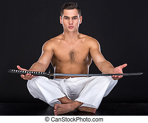 Martial arts - Portrait of a young muscular athlete with a...