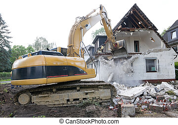 Digger demolishing house - A digger demolishing houses for...